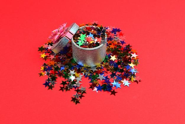 Blaue geschenkbox mit rosa schleife und konfetti auf rotem grund.
