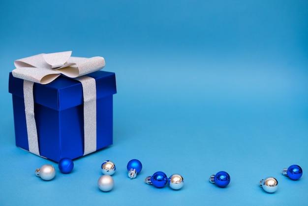 Blaue geschenkbox mit weihnachtskugeln auf einem blauen hintergrundkopierraum