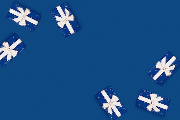 Blaue geschenkboxen auf farbigem hintergrund.