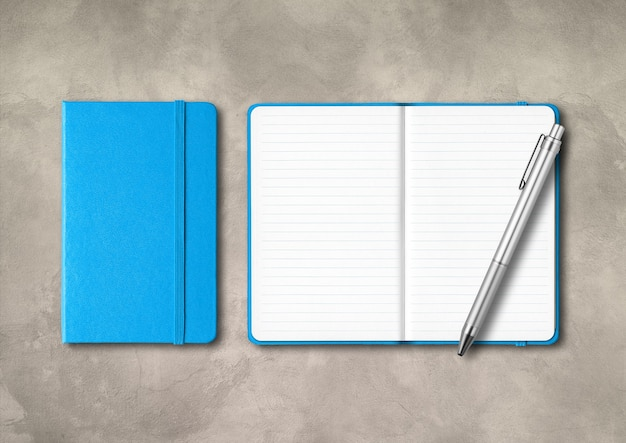 Blaue geschlossene und offene notizbücher mit einem stift. modell lokalisiert auf konkretem hintergrund