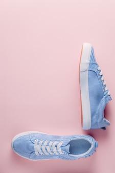 Blaue gestreifte turnschuhe auf rosa pastellhintergrund