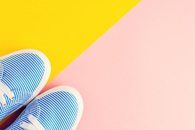 Blaue gestreifte weibliche turnschuhe auf pastellrosa und gelb mit copyspace. flachgelegt, draufsicht