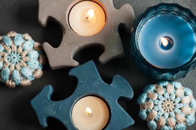 Blaue häkelsteine und brennende kerzen