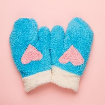 Blaue handschuhe mit herzsymbol auf rosa hintergrund.