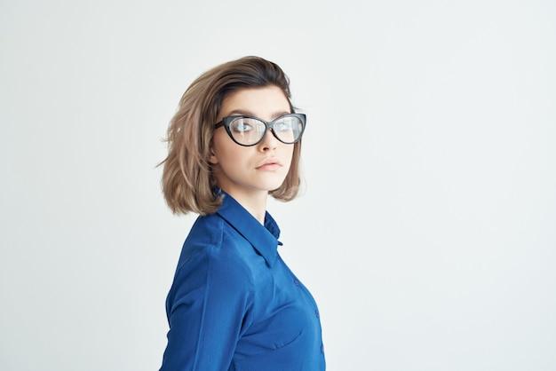 Blaue hemden der frau mit brillenmode, die hellen hintergrund aufwirft