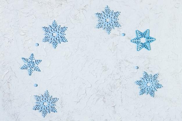 Blaue hölzerne schneeflockenverzierungen auf hellem hintergrund mit silbernem funkeln.