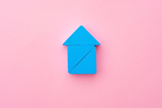 Blaue hölzerne spielzeughausminiatur auf rosa papieroberfläche