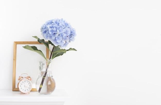 Blaue hortensienblumen in der vase mit holzrahmen im provenzalischen innenraum