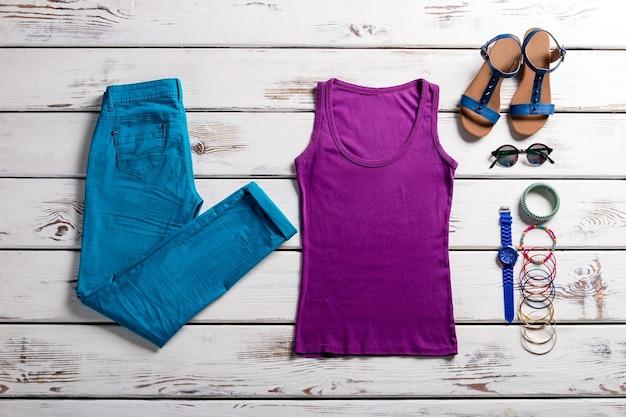 Blaue hose und lila top. bunte kleidung auf hölzernem hintergrund. buntes outfit für den sommer. einfache bunte kleidung für frauen.