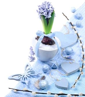 Blaue hyazinthe mit ostern-dekorationen auf weißem, eckelement