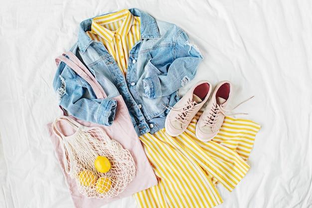 Blaue jeansjacke und gelbes kleid mit öko-tasche und turnschuhen auf weißem bett. stilvolles herbst- oder frühlingsoutfit für damen. trendige kleidung. mode-konzept. flache lage, ansicht von oben.
