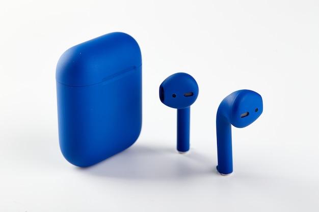 Blaue kabellose kopfhörer-airpods in ladekoffer-nahaufnahme