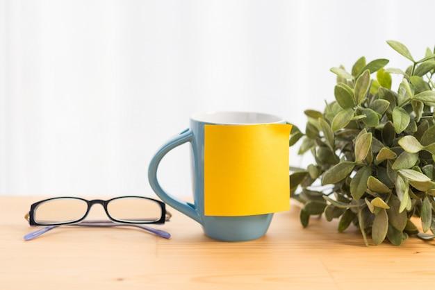 Blaue kaffeetasse, brille und gelbes post-it für text auf holztischplatte