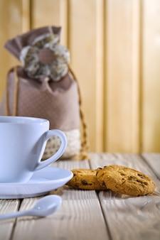 Blaue kaffeetasse mit keksen und tasche