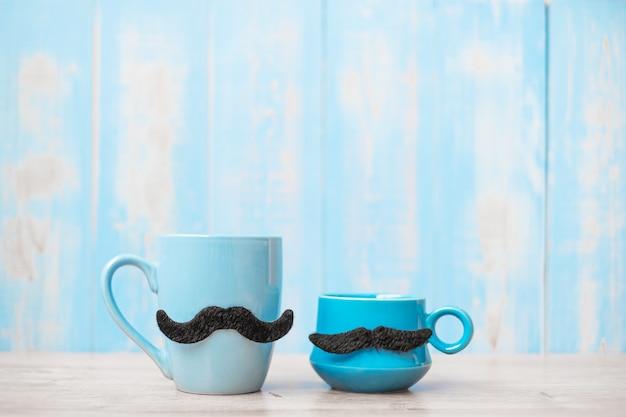 Blaue kaffeetassen mit schwarzem schnurrbart auf holztischhintergrund am morgen. vatertag und internationales männertagskonzept