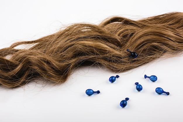 Blaue kapseln mit vitaminen für haar liegen auf braunen haarlocken