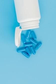 Blaue kapseln, pillen an einer blauen wand. kapseln in einem weißen glas. vitamine, nahrungsergänzungsmittel für die gesundheit von frauen