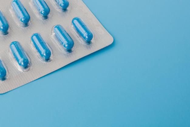 Blaue kapseln, pillen an einer blauen wand. vitamine, nahrungsergänzungsmittel für die gesundheit von frauen