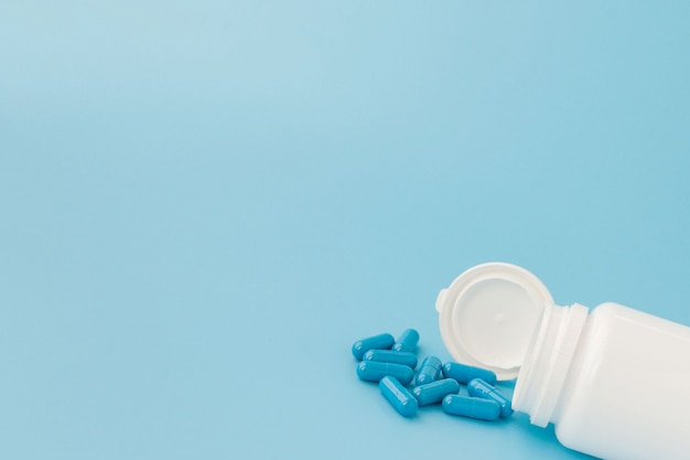 Blaue kapseln, pillen auf einem blauen hintergrund. kapseln in einem weißen glas. vitamine, nahrungsergänzungsmittel für die gesundheit von frauen