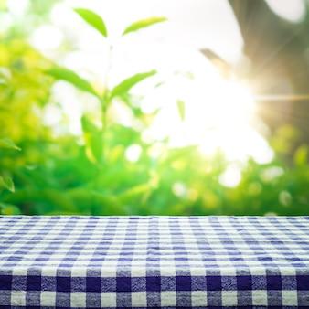 Blaue karierte tischdecke textur draufsicht mit abstraktem grün vom garten