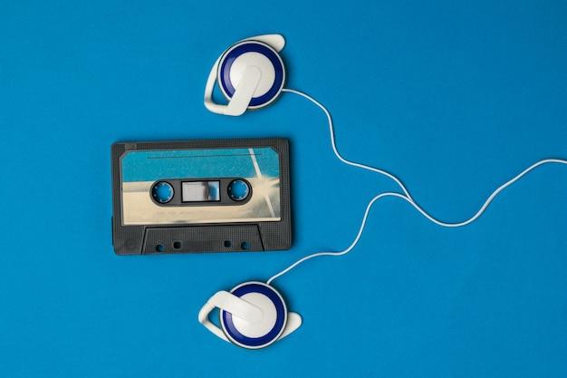 Blaue kassette mit magnetband und blauen kopfhörern auf blau