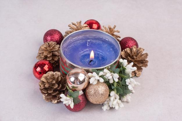 Blaue kerze mit weihnachtskugeln und tannenzapfen