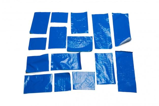 Blaue klebebandstücke lokalisiert auf weiß.