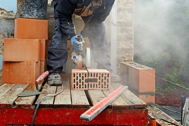 Blaue klollararbeitskraft, die betonblock mit elektrischer säge schneidet