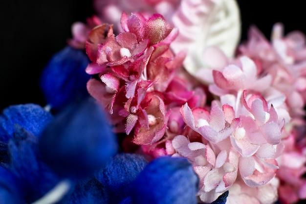 Blaue knospen und rosa flieder auf schwarzem hintergrund. künstliche blumen