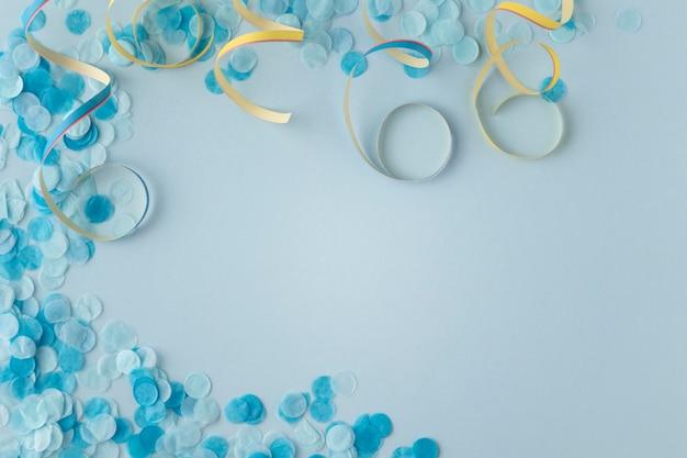 Blaue konfetti und bänder des karnevalspapiers kopieren platz