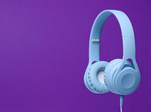 Blaue kopfhörer des 3d-surround-fotos auf lila hintergrund