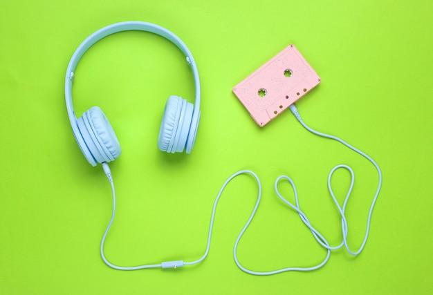 Blaue kopfhörer mit kabel in audiokassette auf grünem hintergrund