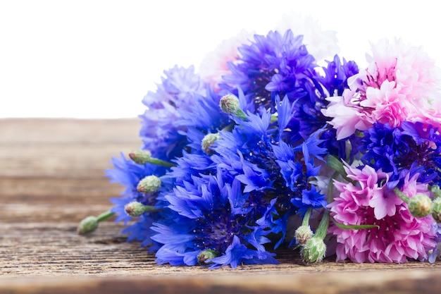 Blaue kornblumen auf holztisch