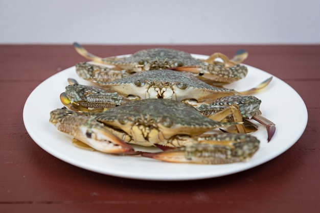 Blaue krabben auf platte, auf einem hölzernen hintergrund