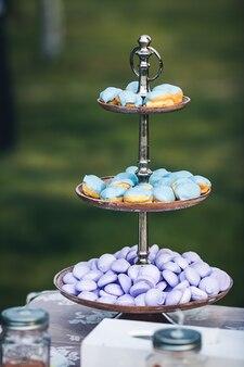 Blaue kuchen und lila makronen auf einem schönen metallständer.