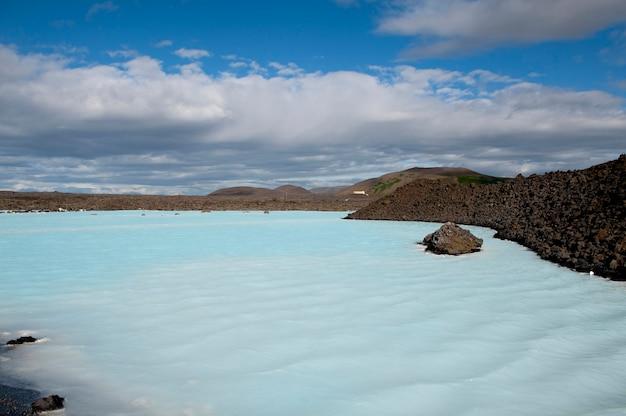 Blaue lagune mit felsiger küstenlinie unter einem hellen blauen bewölkten himmel