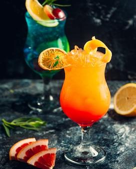 Blaue lagune und orange cocktails mit fruchtscheiben.