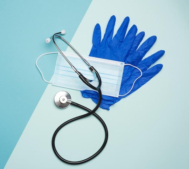 Blaue latexhandschuhe und einwegmasken auf blauem hintergrund