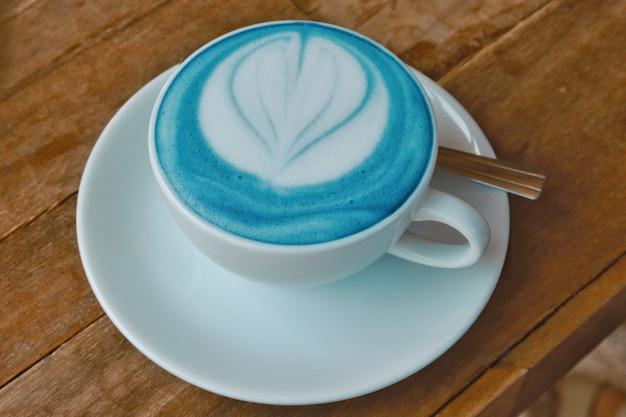 Blaue latte-kunst der nahaufnahme auf holztisch