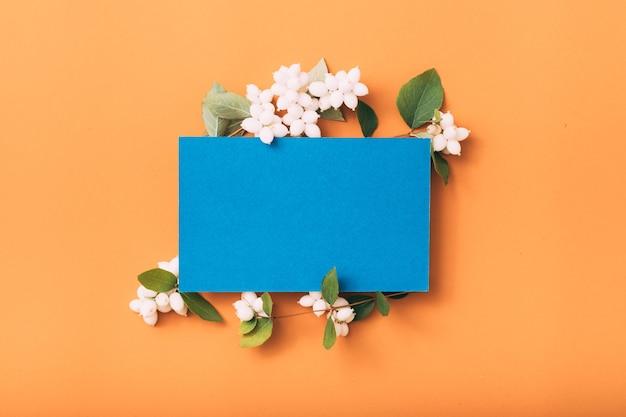 Blaue leere papiernotiz oder karte mit misteldekor.