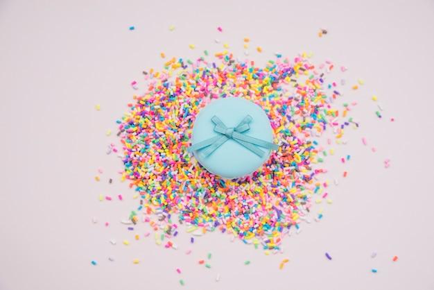Blaue macarons über den bunten besprüht auf farbigem hintergrund