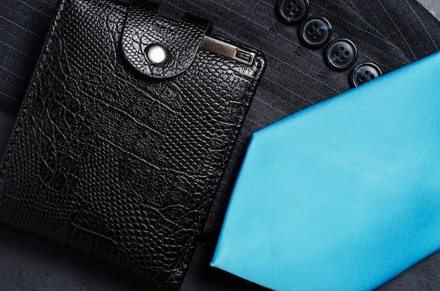 Blaue männerkrawatte, jackenärmel und schwarze brieftasche. konzeptbild eines erfolgreichen geschäftsmannes
