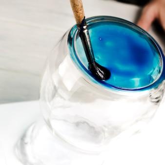 Blaue malerei erfolgt auf glasgefäß mit pinsel