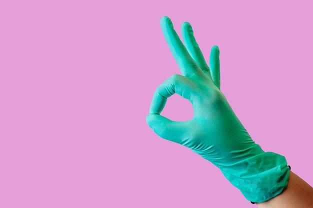 Blaue medizinische latexhandschuhe an einer weiblichen hand, zeigt ok-geste