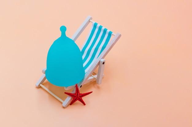 Blaue menstruationstasse mit einem blauen liegestuhl auf einem pfirsichpastellhintergrund.