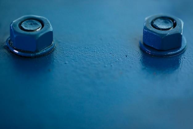 Blaue metall rauhe oberfläche des teils mit schrauben und muttern. blau lackiert von autoteil. hintergrundbild des automobilschmutzes.