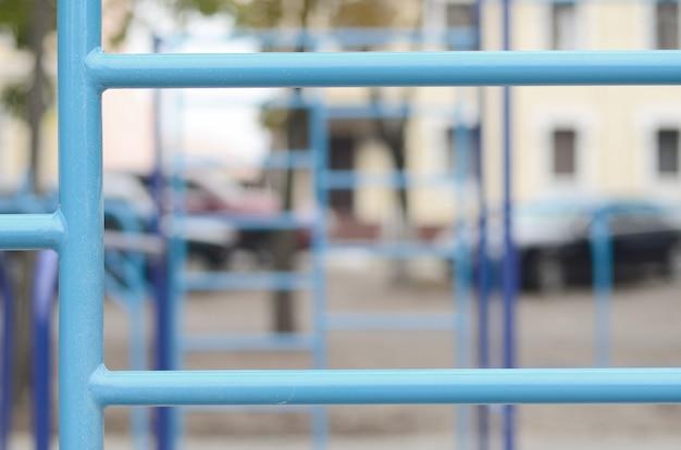 Blaue metallrohre und querstangen gegen ein straßensportfeld für die ausbildung in der leichtathletik.