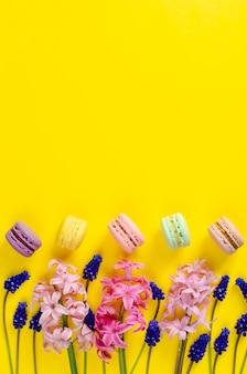 Blaue muscariblumen, rosa hyazinthe und macarons oder makronen auf gelbem hintergrund. platz für text. von oben nach unten. flach liegen. grußkarten-konzept