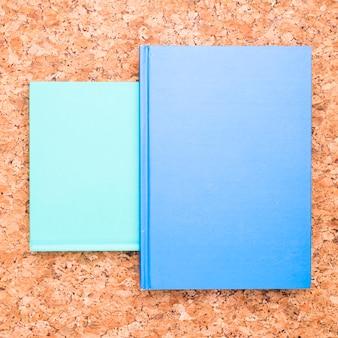 Blaue notizbücher auf hölzernem schreibtisch