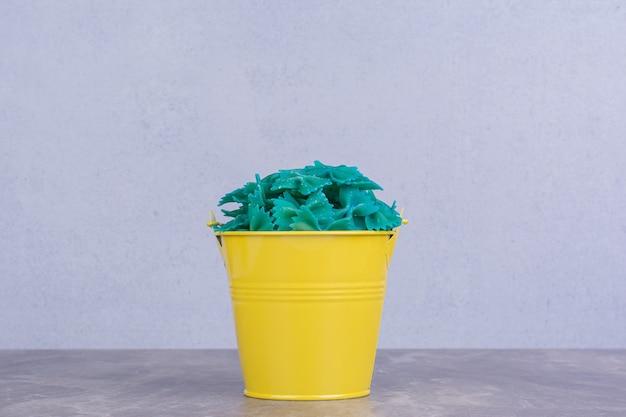 Blaue nudeln in einem gelben metalleimer